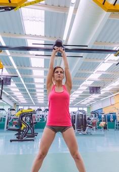 Ritratto di bella donna che solleva kettlebell di ferro nero in un allenamento crossfit su fitness center