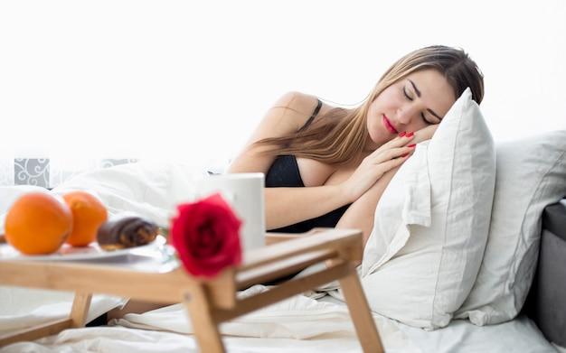 Ritratto di bella donna sdraiata a letto e facendo colazione in camera d'albergo