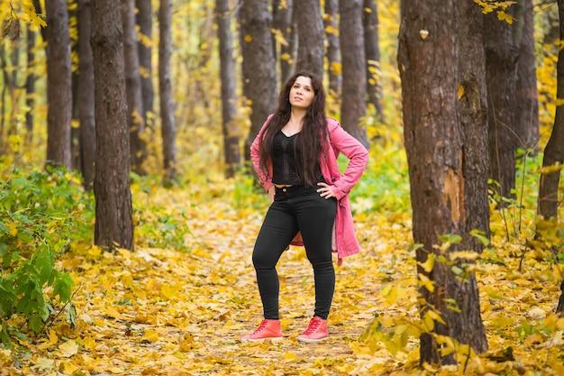 Ritratto di bella donna in giacca rosa nel parco Foto Premium