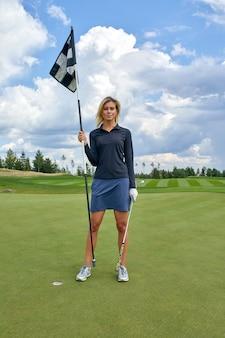 Ritratto di bella donna che gioca a golf su un fondo verde del campo all'aperto