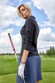 Ritratto di bella donna che gioca a golf su uno spazio verde del campo all'aperto. il concetto di golf, la ricerca dell'eccellenza, l'eccellenza personale, lo sport reale.