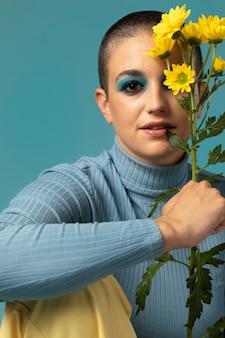 Ritratto di bella donna che posa in un dolcevita con fiori gialli