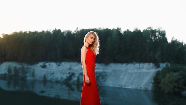 Ritratto di una bella donna in un abito rosso su una montagna vicino al fiume