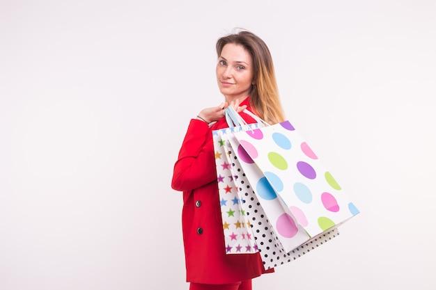 Ritratto di bella donna in giacca rossa con borse della spesa sulla schiena
