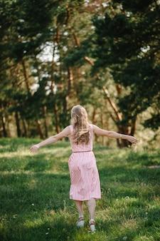 Ritratto di una bella donna scappare nell'erba verde sul campo, la natura durante le vacanze estive. il gioco nel parco all'ora del tramonto. avvicinamento.