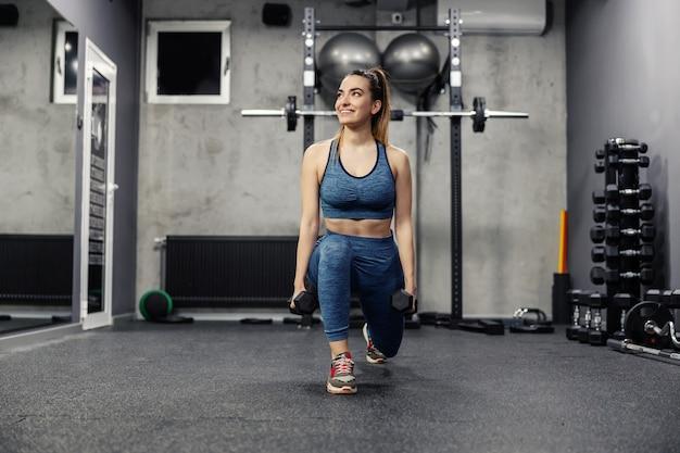 Ritratto di una bella donna in abbigliamento sportivo e in buona forma fisica facendo squat in una palestra interna isolata