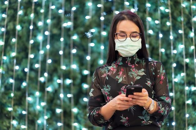 Ritratto una bella donna in piedi con un telefono cellulare per controllare la posta elettronica e indossare la maschera per il viso con sfondo sfocato bokeh