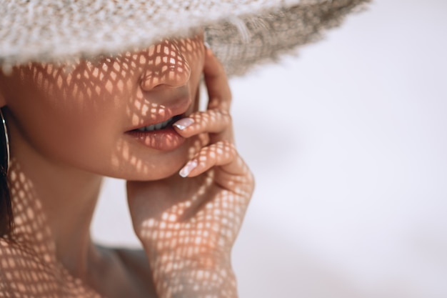Ritratto di una bella donna in un cappello di paglia con french manicure
