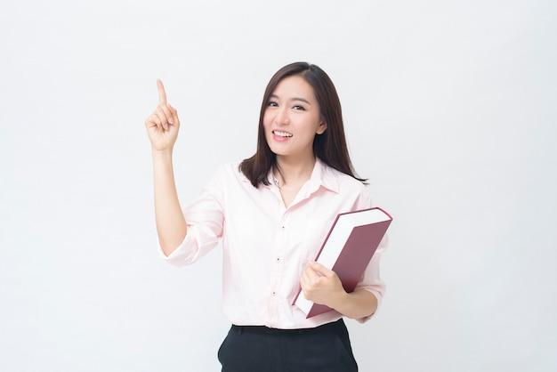 Ritratto di bella studentessa in camicia rosa è in possesso di un libro isolato su sfondo bianco studio