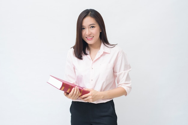 Ritratto di bella studentessa in camicia rosa è in possesso di un libro isolato