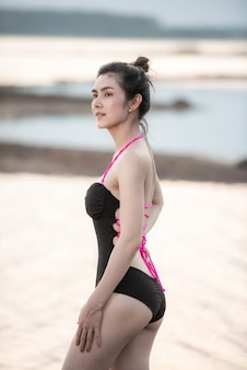 Ritratto bella donna in costume da bagno con un costume da bagno intero bellissimo corpo sportivo che cammina e posa su una spiaggia