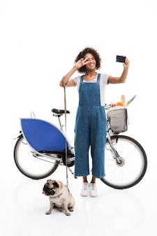 Ritratto di bella donna che prende selfie ritratto sullo smartphone mentre sta in piedi con il suo carlino e la bicicletta isolati su un muro bianco