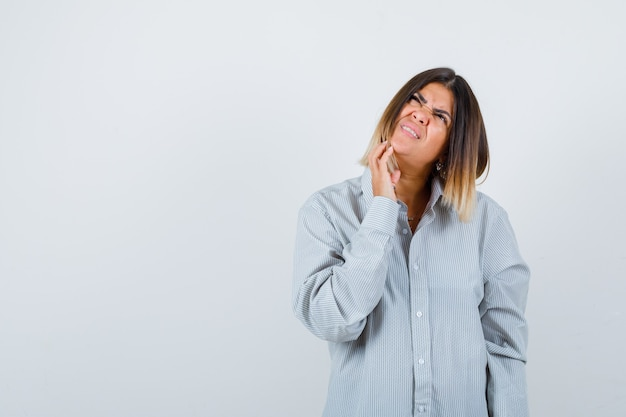 Ritratto di bella donna che tocca il mento mentre guarda in camicia e guarda confusa vista frontale