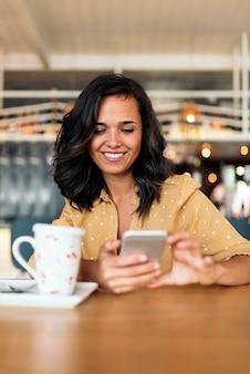 Ritratto di bella donna che utilizza cellulare nella caffetteria.