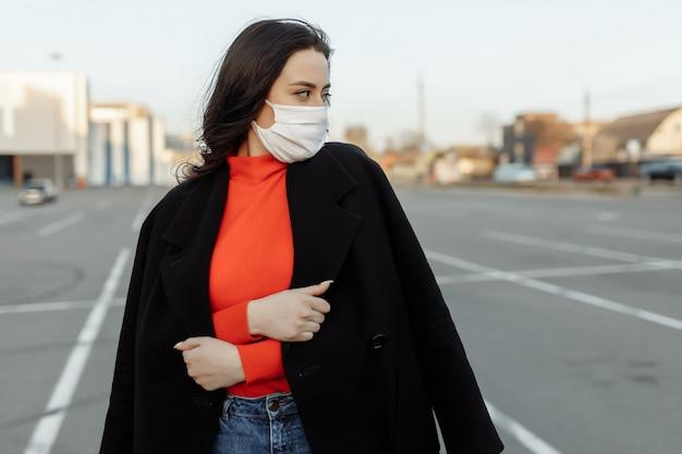 Ritratto di bella donna che cammina per strada indossando maschera protettiva come protezione contro le malattie infettive.