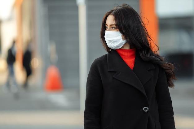 Ritratto di bella donna che cammina per strada indossando maschera protettiva come protezione contro