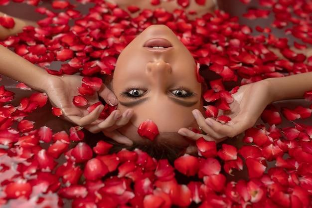 Ritratto di bella donna in acqua con il petalo di rosa, concetto della stazione termale, ritratto alto vicino