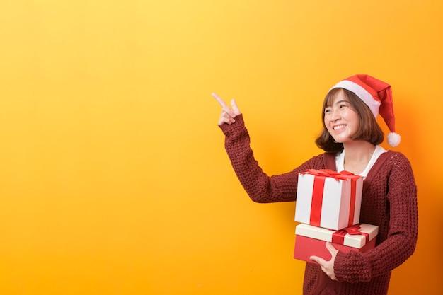 Un ritratto di bella donna che indossa il cappello rosso di babbo natale tenendo il contenitore di regalo su sfondo di studio, natale e capodanno concetto