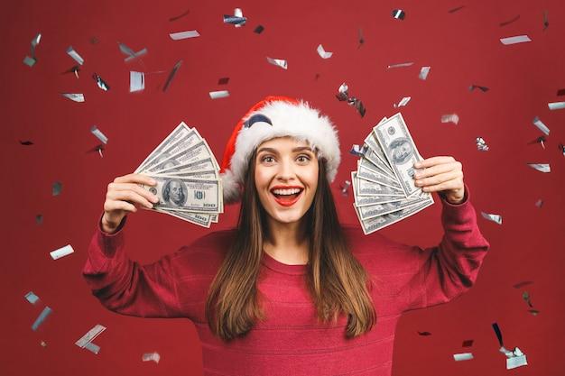 Ritratto di bella donna che indossa il cappello della santa e che tiene le banconote del dollaro