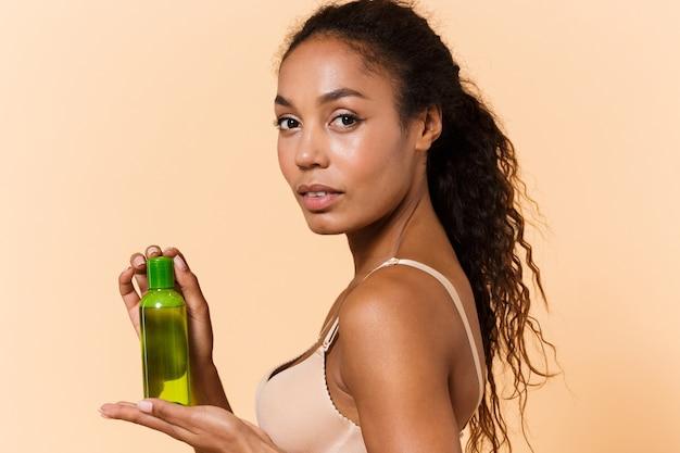 Ritratto di bella donna che indossa lingerie bianca tenendo la bottiglia con cosmetici, mentre in piedi isolato sul muro beige