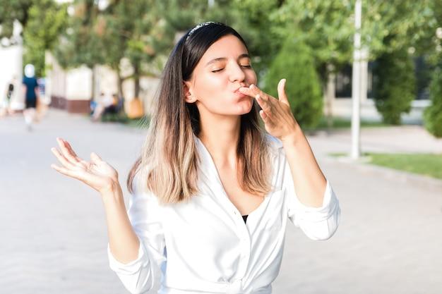 Ritratto di bella donna in camicia bianca e castone per capelli con la bocca piena di cibo leccandosi le dita all'aperto nel parco cittadino e godendo di cibo spazzatura ma gustoso mentre cammina