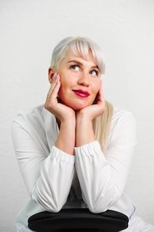 Ritratto di una bella donna in abito bianco su sfondo chiaro un gesto di pianificazione sognante ad occhi aperti...