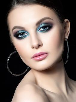 Ritratto di bella donna con il trucco di moda. i moderni occhi blu smokey si compongono.