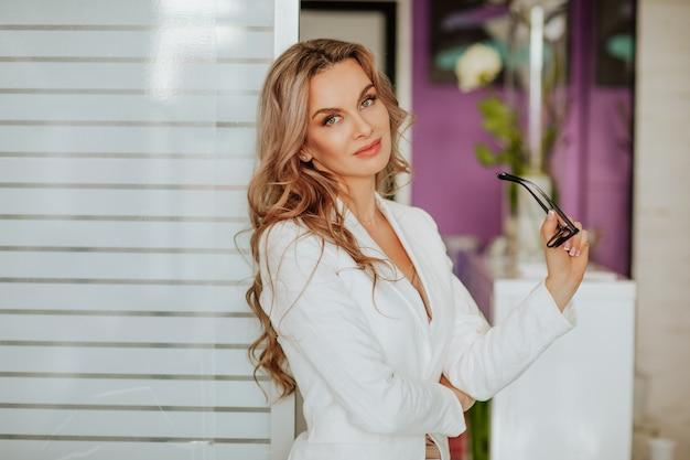 Ritratto di bella donna con capelli ricci lunghi in giacca da ufficio bianca in posa con gli occhiali nell'armadio