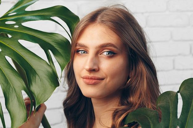 Ritratto di una bella donna con foglie di monstera. foto creativa