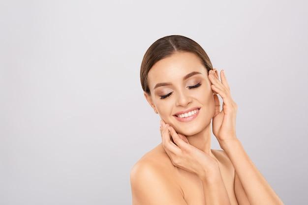 Ritratto di bella donna con trucco naturale toccando il suo viso.