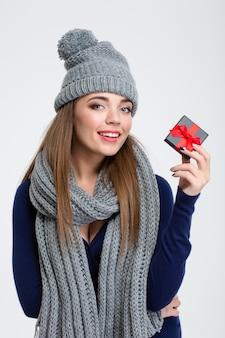 Ritratto di una bella donna con sciarpa e cappello che tiene in mano una confezione regalo di gioielli isolata su uno sfondo bianco
