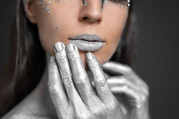 Ritratto di una bella donna con vernice argento sulla pelle e sui capelli.