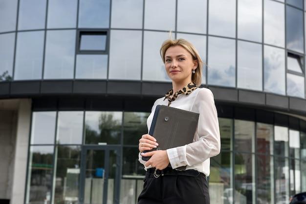 Ritratto di bella donna con tablet all'aperto vicino al grande centro ufficio