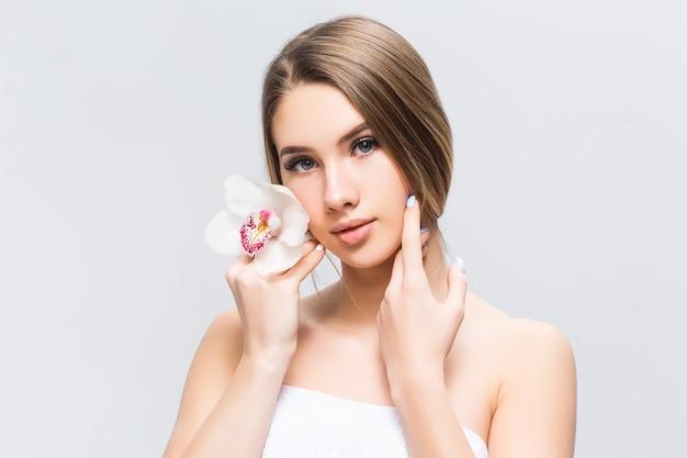 Ritratto di bella donna con fiore bianco tra i capelli
