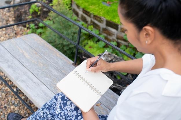 Ritratto di una bella donna che scrive in un libro è seduto a pensare al lavoro al parco, rilassarsi concetto di tempo all'aperto.