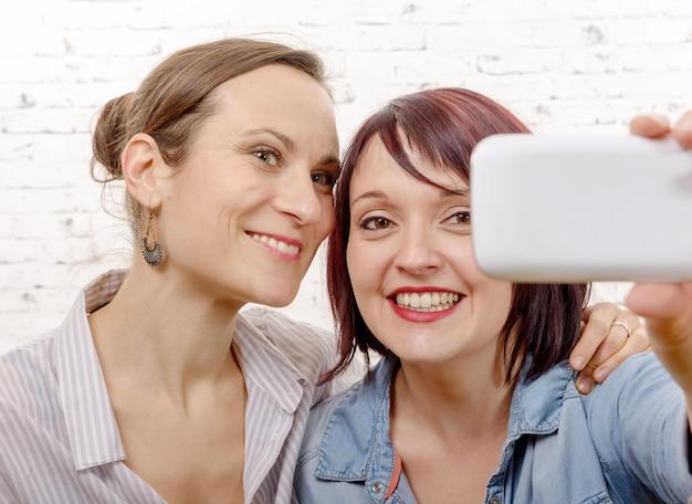 Ritratto di belle donne che fanno i selfie a casa