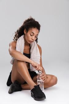Ritratto di una bella giovane sportiva africana che riposa dopo l'allenamento isolato sopra il muro grigio, acqua potabile