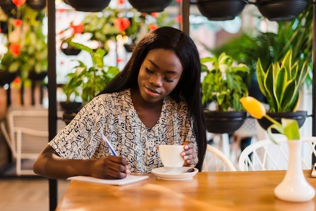 Ritratto di giovane e bella donna africana seduto al caffè e scrivere note