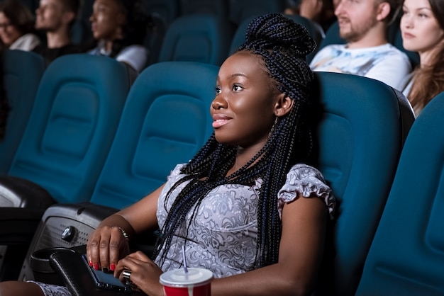 Ritratto di una bellissima giovane donna africana sorridente guardando lo schermo attentamente mentre vi godete la visione di un film al cinema locale
