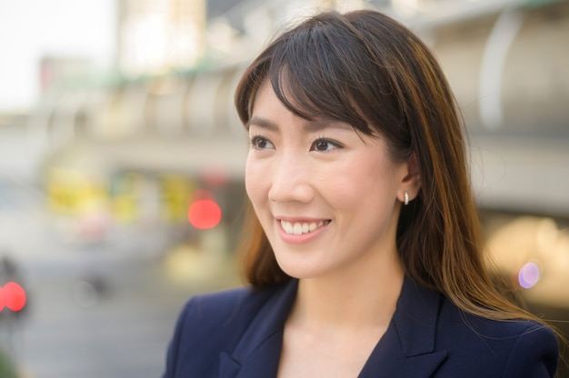 Il ritratto di bella giovane donna asiatica di affari sta lavorando nella città moderna