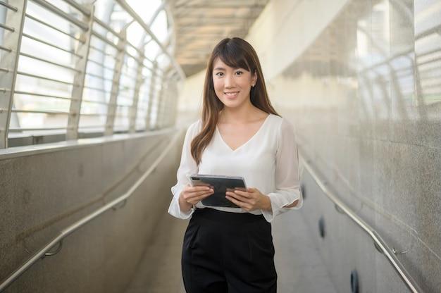 Il ritratto di bella giovane donna asiatica di affari sta lavorando nella città moderna Foto Premium