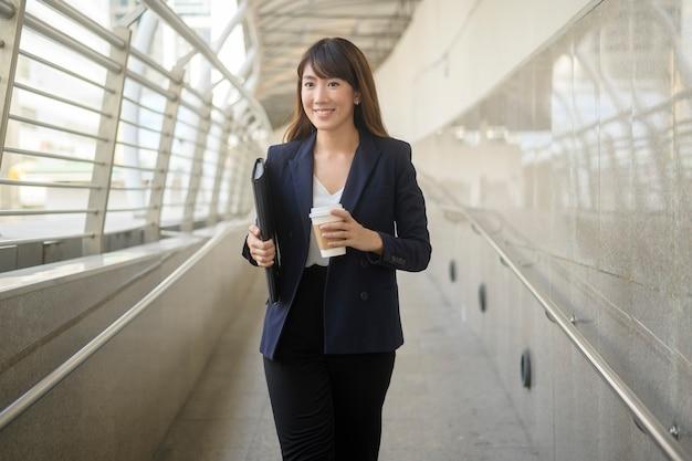 Il ritratto di bella giovane donna d'affari asiatica sta lavorando nella città moderna modern