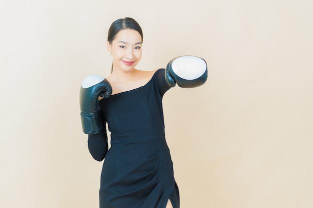 Ritratto di bella giovane donna asiatica boxe con guanto su giallo