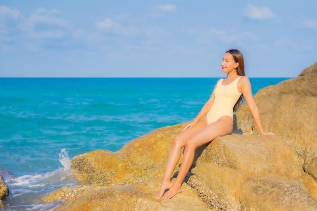 La bella giovane donna asiatica del ritratto si rilassa il tempo libero di sorriso intorno all'oceano del mare della spiaggia sul viaggio di vacanza di viaggio