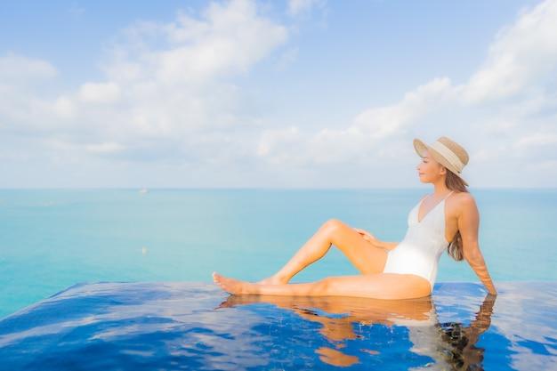 La bella giovane donna asiatica del ritratto si rilassa il tempo libero di sorriso intorno alla piscina all'aperto nella località di soggiorno dell'hotel sulla vacanza di viaggio