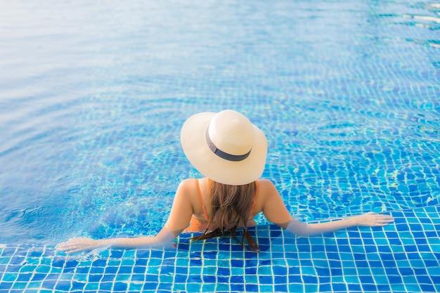 La bella giovane donna asiatica del ritratto si rilassa il tempo libero di sorriso intorno alla piscina all'aperto nell'hotel della località di soggiorno con la vista dell'oceano del mare