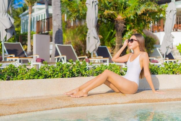 La bella giovane donna asiatica del ritratto si rilassa il tempo libero di sorriso intorno alla piscina all'aperto con l'oceano del mare nella vacanza di viaggio