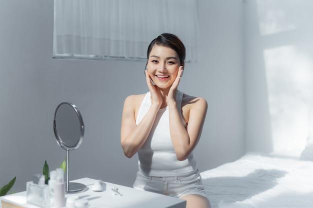 Il ritratto di bella giovane donna asiatica sorride mentre sveglia sano e benessere con l'alba al mattino in camera da letto