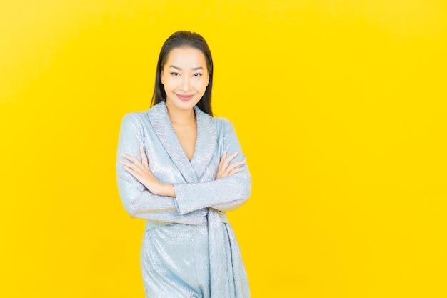 Sorriso di bella giovane donna asiatica del ritratto con azione sulla parete gialla
