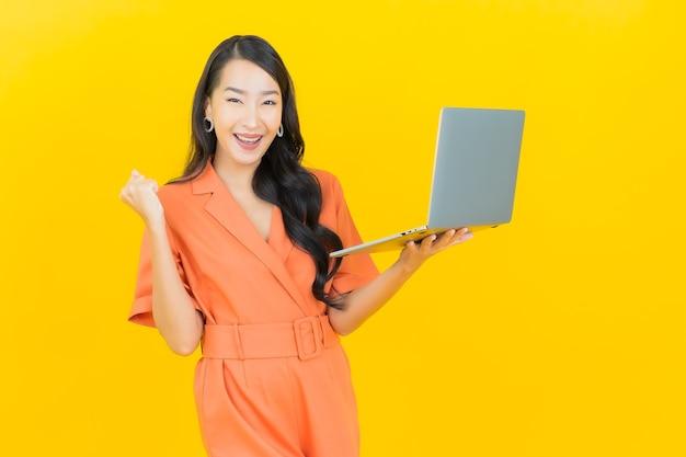 Sorriso della bella giovane donna asiatica del ritratto con il computer portatile del computer su colore giallo